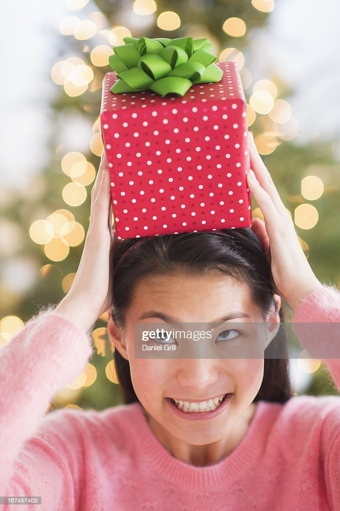 USA, New Jersey, Jersey City, Front view of teenage girl ( 16-17 years) holding Christmas gift on head : Stock Photo