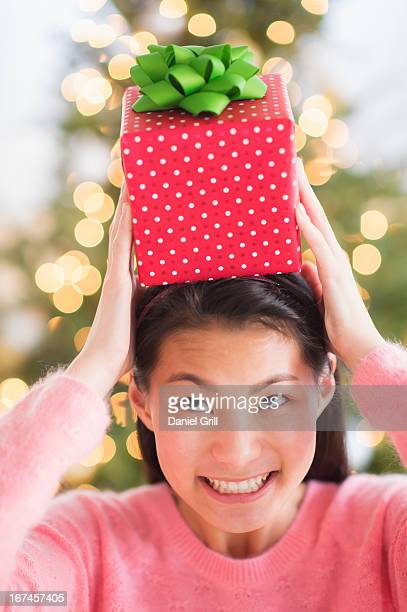 usa, new jersey, jersey city, front view of teenage girl ( 16-17 years) holding christmas gift on head - 16 17 years stock pictures, royalty-free photos & images