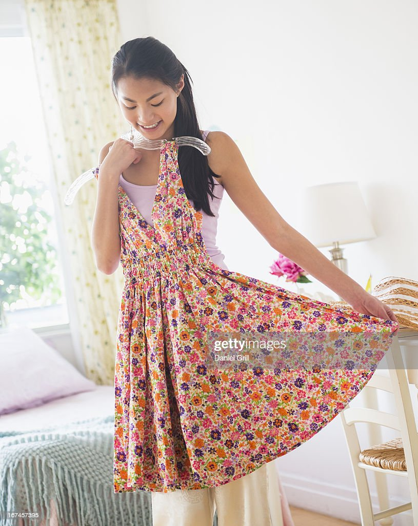 USA, New Jersey, Jersey City, Front view of teenage girl ( 16-17 years) trying on dress : Stock Photo