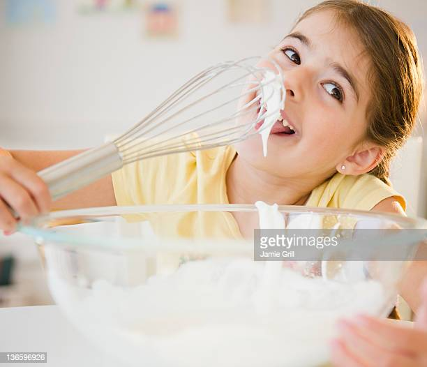 USA, New Jersey, Jersey City, Girl ( 6-7) licking whipped cream from whisk
