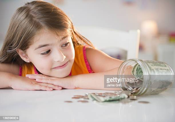 USA, New Jersey, Jersey City, Girl ( 6-7) looking at savings in jar