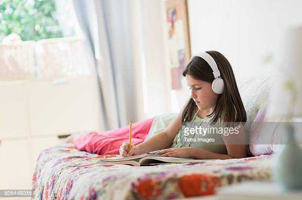 USA, New Jersey, Jersey City, Girl (10-11) lying in bed and writing in notebook
