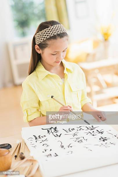 USA, New Jersey, Jersey City, Girl (8-9) painting japanese symbols