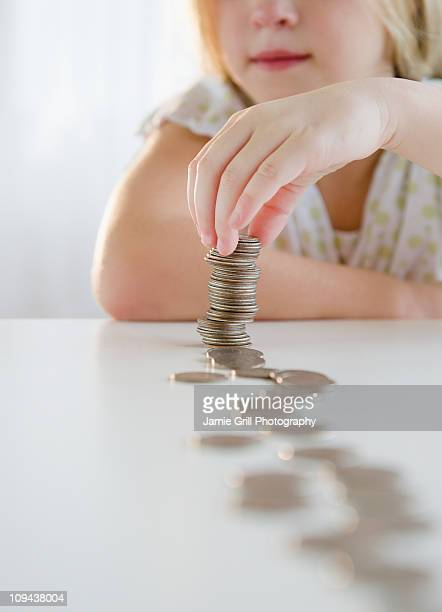 USA, New Jersey, Jersey City, Girl (8-9) playing with coins