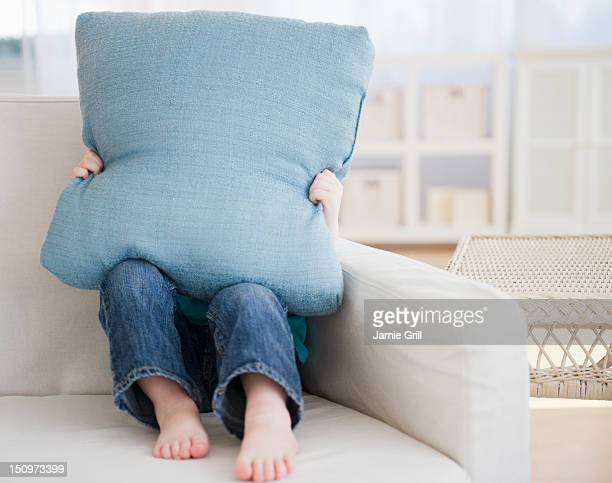 USA, New Jersey, Jersey City, Girl (2-3) sitting on sofa hiding behind pillow