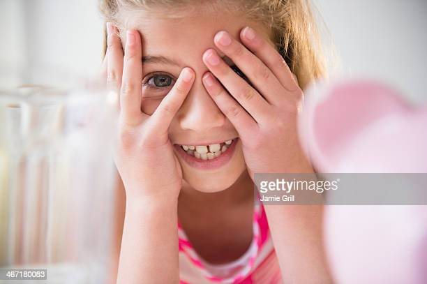USA, New Jersey, Jersey City, Girl (8-9) smiling and covering eyes