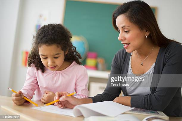 USA, New Jersey, Jersey City, girl (6-7) with female teacher sitting at desk in classroom
