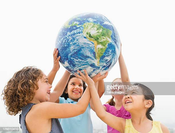 USA, New Jersey, Jersey City, Girls (6-9) holding globe