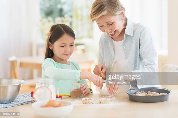 USA, New Jersey, Jersey City, Granddaughter (8-9) cooking with grandmother