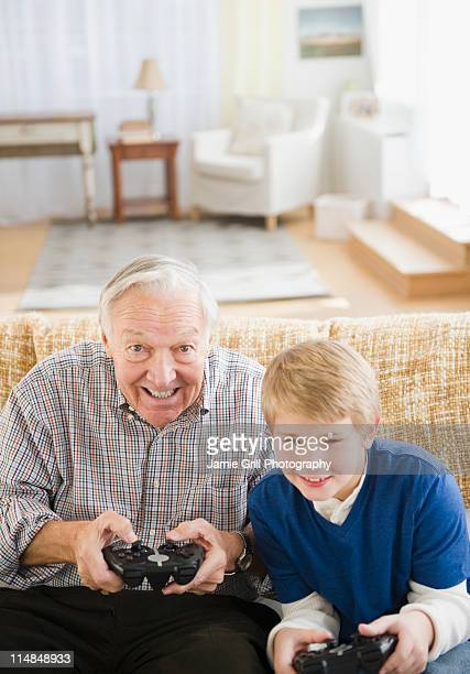 USA, New Jersey, Jersey City, grandfather and grandson (8-9) playing video games