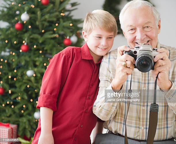 USA, New Jersey, Jersey City, grandfather and grandson (8-9 years) taking picture, christmas tree in background