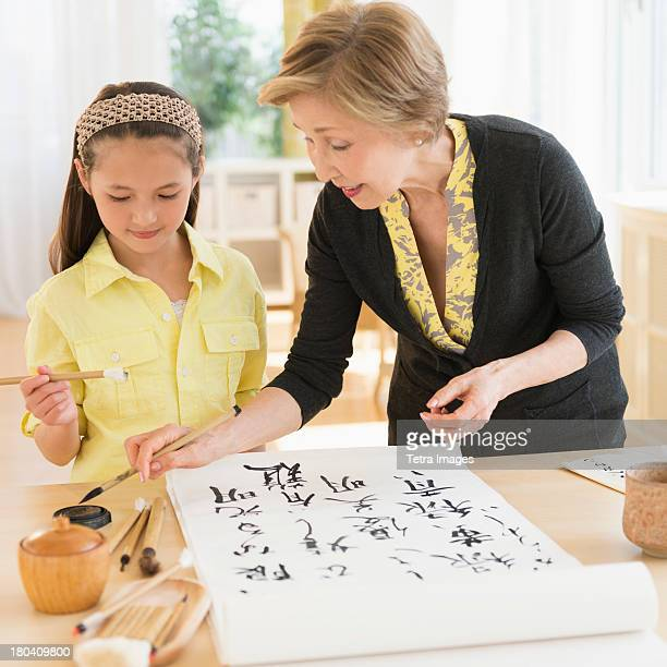 usa, new jersey, jersey city, grandmother and granddaughter (8-9) painting japanese symbols - 日本語の文字 ストックフォトと画像
