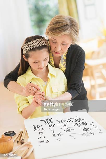 USA, New Jersey, Jersey City, Grandmother and granddaughter (8-9) painting japanese symbols