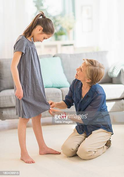 USA, New Jersey, Jersey City, Grandmother attaching sewing pins to granddaughter's (8-9) dress