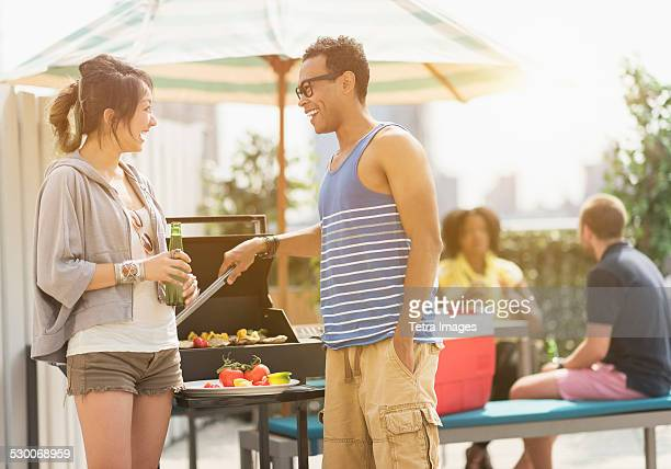 USA, New Jersey, Jersey City, Group of friends enjoying barbeque