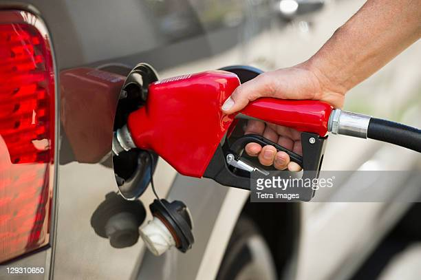 USA, New Jersey, Jersey City, Hand holding fuel pump refueling car