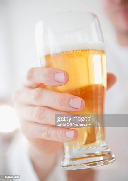 USA, New Jersey, Jersey City, hand holding glass of beer