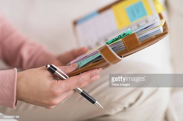 USA, New Jersey, Jersey City, Hands holding personal organizer