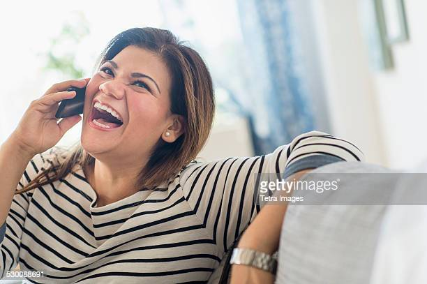 USA, New Jersey, Jersey City, Happy woman sitting on sofa with mobile phone