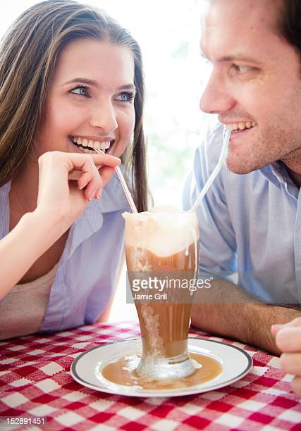 USA, New Jersey, Jersey City, Happy young couple drinking milk shake