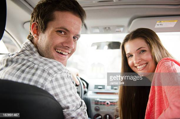 USA, New Jersey, Jersey City, Happy young couple sitting in car