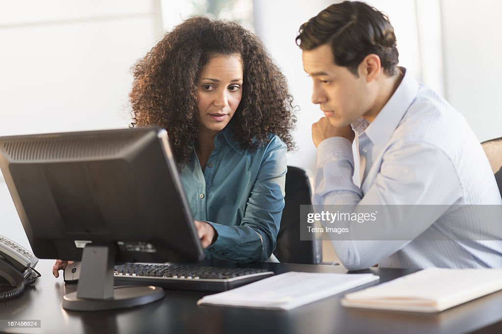 USA, New Jersey, Jersey City, Man and woman working at desk in office : Stock Photo