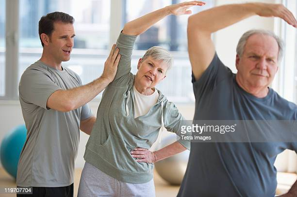 USA, New Jersey, Jersey City, Man assisting senior people exercising