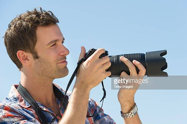 USA, New Jersey, Jersey City, Man holding camera against blue sky
