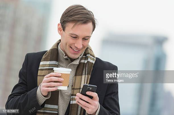 USA, New Jersey, Jersey City, Man in winter clothes looking at phone