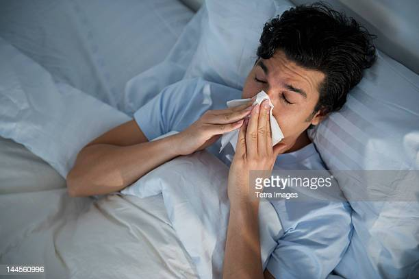 usa, new jersey, jersey city, man lying in bed and blowing nose - resfriado y gripe fotografías e imágenes de stock