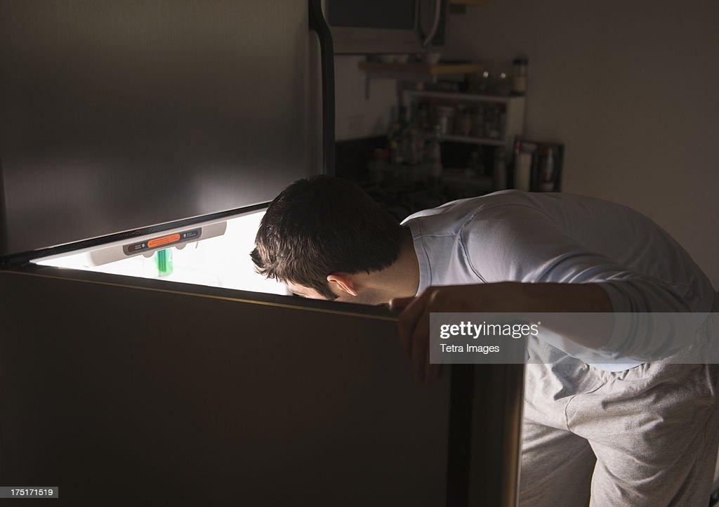 USA, New Jersey, Jersey City, Man opening fridge at night : Stock Photo