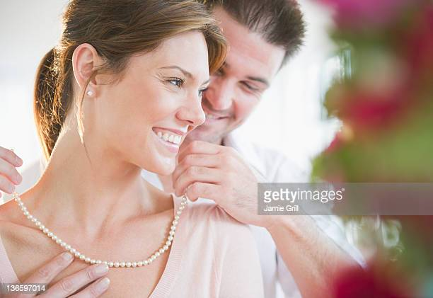usa, new jersey, jersey city, man putting pearls on his girlfriend's neck - pearl necklace stock pictures, royalty-free photos & images
