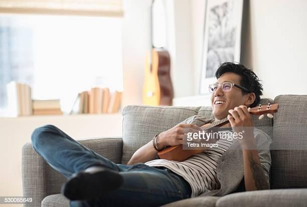 USA, New Jersey, Jersey City, Man sitting on sofa and playing ukulele