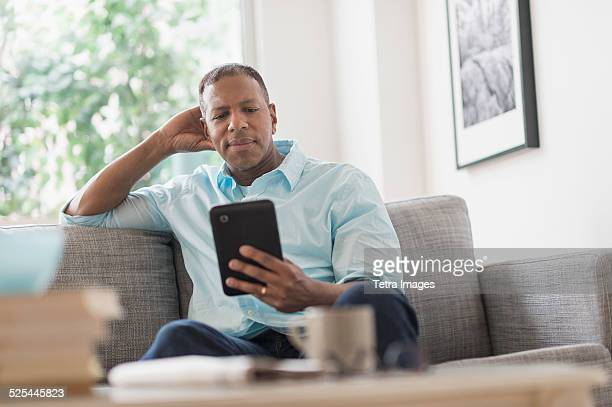 USA, New Jersey, Jersey City, Man sitting on sofa at home and using digital tablet