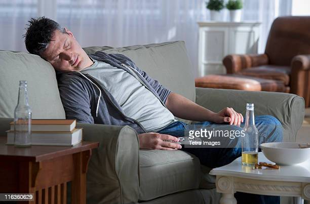 usa, new jersey, jersey city, man sitting on sofa, holding remote control and sleeping - man cave stock pictures, royalty-free photos & images