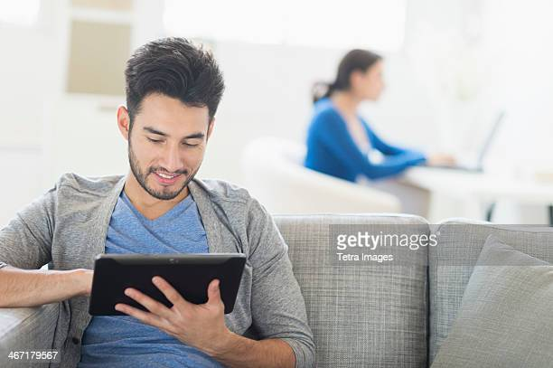 USA, New Jersey, Jersey City, Man sitting on sofa using digital tablet at home, woman in background