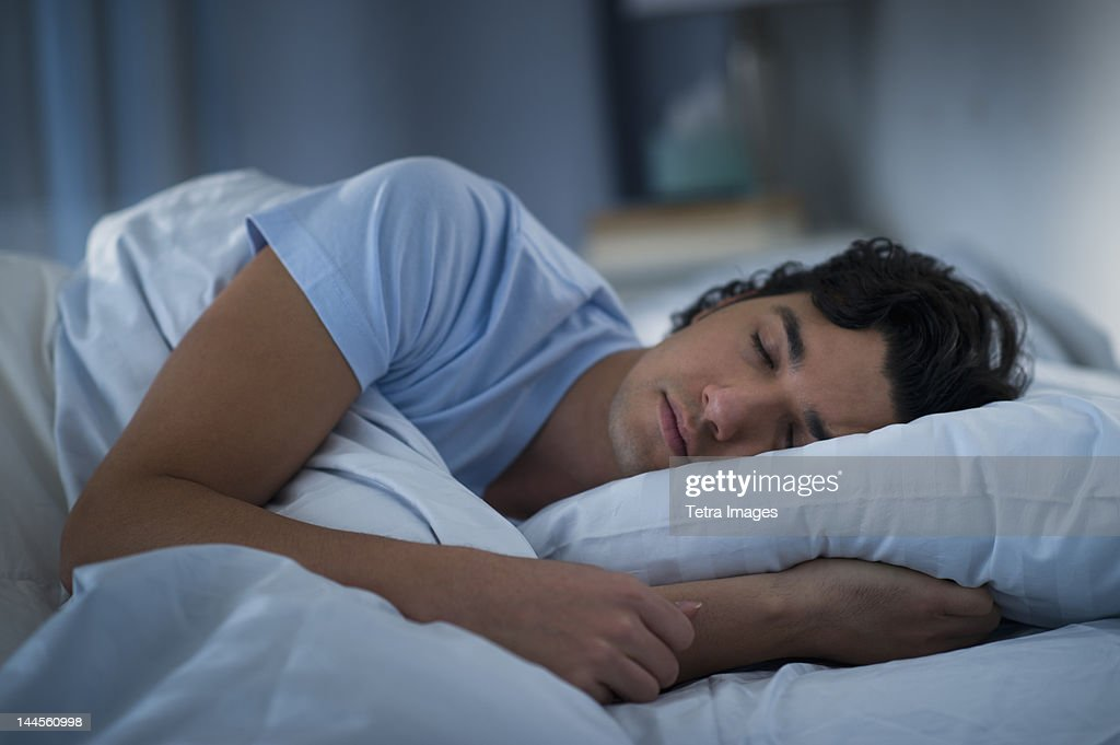 USA, New Jersey, Jersey City, Man sleeping in bed : Stock Photo