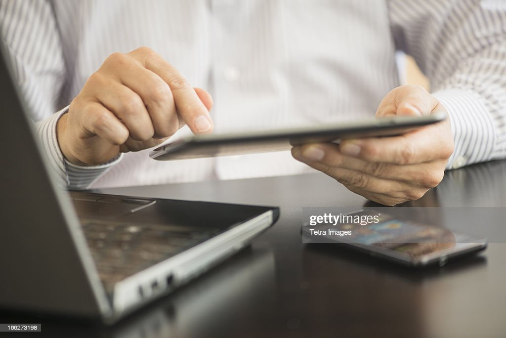 USA, New Jersey, Jersey City, Man using tablet pc, laptop and smartphone : Stock Photo