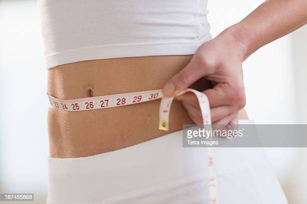 usa, new jersey, jersey city, midsection of woman measuring waistline - slim stock pictures, royalty-free photos & images