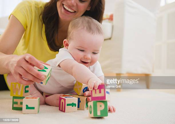 USA, New Jersey, Jersey City, Mother and baby daughter (6-11 months) playing with blocks