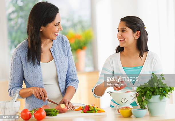 USA, New Jersey, Jersey City, Mother and daughter (12-13) cooking in kitchen