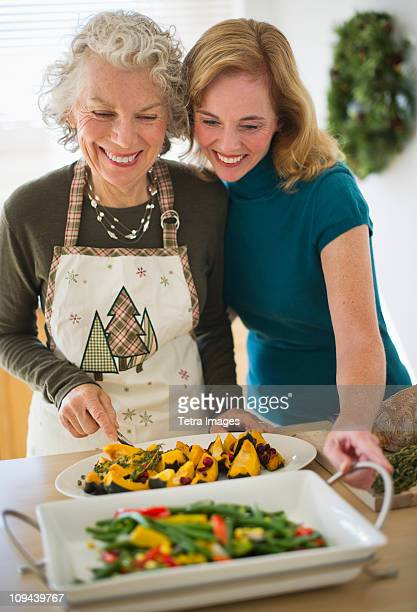 USA, New Jersey, Jersey City, Mother and daughter preparing food in kitchen