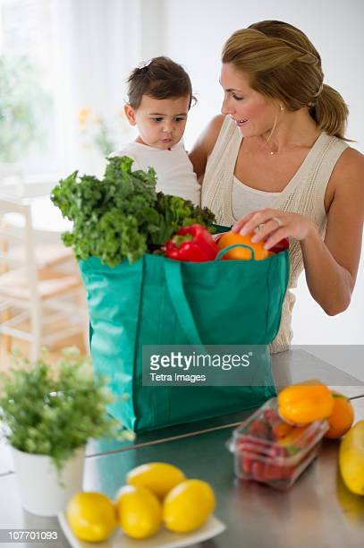USA, New Jersey, Jersey City, Mother and daughter (12-18 months) unpacking shopping bag