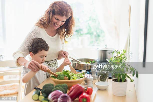 usa, new jersey, jersey city, mother and son (6-7) cooking together - voorbereiding stockfoto's en -beelden