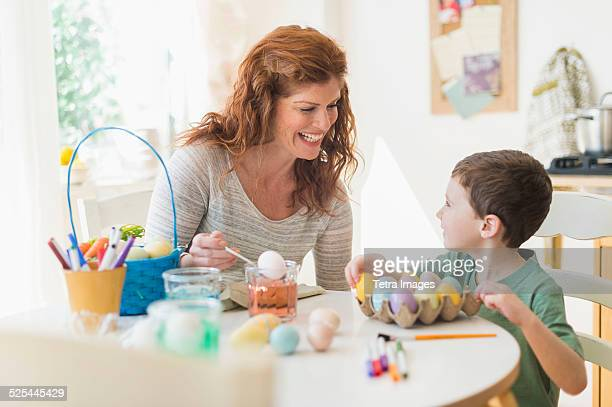 USA, New Jersey, Jersey City, Mother and son (6-7) painting Easter eggs