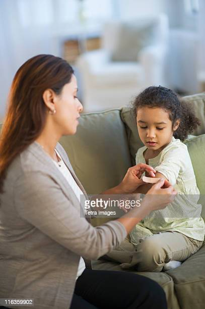USA, New Jersey, Jersey City, mother applying bandaid on daughter's (6-7) arm