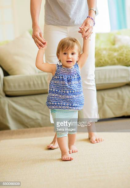 usa, new jersey, jersey city, mother assisting baby daughter (18-23 months) with her first steps - 18 23 meses fotografías e imágenes de stock