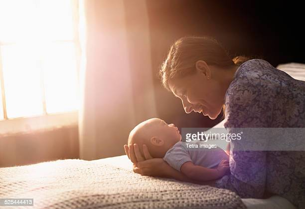 usa, new jersey, jersey city, mother holding baby boy (2-5 months ) in bedroom - 2 5 months stock pictures, royalty-free photos & images