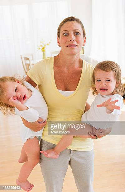 USA, New Jersey, Jersey City, Mother holding crying daughters (2-3) and making facial expression