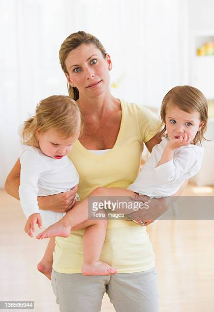 USA, New Jersey, Jersey City, Mother holding daughters (2-3) and making facial expression